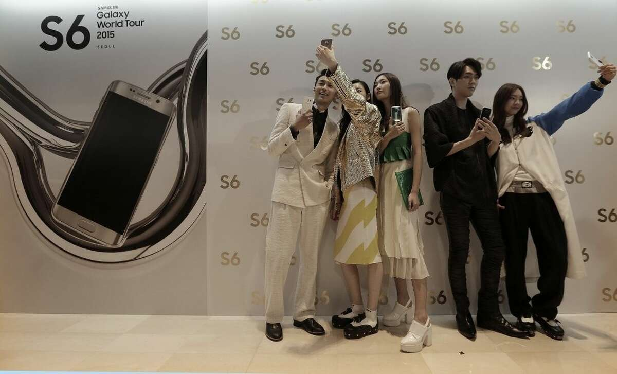 """Models pose with Samsung Electronics Co.'s Galaxy S6 and S6 Edge smartphones during its launch event at company's headquarter in Seoul, South Korea, Thursday, April 9, 2015. When Samsung dubbed development of its latest smartphones """"Project Zero,"""" it was sounding a note of desperation as sales tumbled and it lost pole position in the crucial Chinese market to rivals Xiaomi and Apple. (AP Photo/Ahn Young-joon)"""