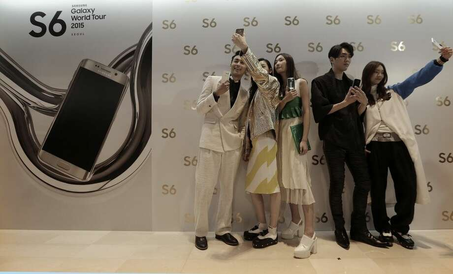 "Models pose with Samsung Electronics Co.'s Galaxy S6 and S6 Edge smartphones during its launch event at company's headquarter in Seoul, South Korea, Thursday, April 9, 2015. When Samsung dubbed development of its latest smartphones ""Project Zero,"" it was sounding a note of desperation as sales tumbled and it lost pole position in the crucial Chinese market to rivals Xiaomi and Apple. (AP Photo/Ahn Young-joon)"
