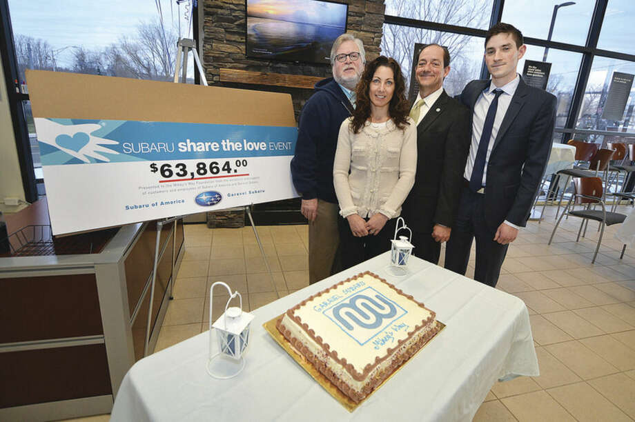 Hour Photo/Alex von KleydorffLes and Cathy Friedman with Mikey's Way Foundation accept a donation from Garavel Subaru and owner Paul Garavel and general manager Jeremy Garavel at their car dealersip on Tindal Ave in Norwalk.
