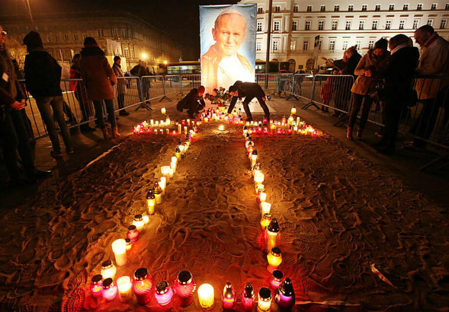 People pray and light candles before a portrait of Polish-born Pope John Paul II in Warsaw, Poland, on Wednesday, April 2, 2014 to mark nine years since the death of the much-loved pontiff who will be made a saint in a Vatican ceremony on April 27. (AP Photo/Czarek Sokolowski)