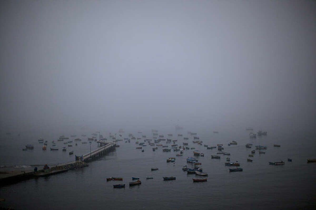 Morning fog lifts at the Chorrillo dock in the Pacific Ocean, revealing small scale fishing boats in Lima, Peru, Wednesday, April 2, 2014. Chilean authorities discovered surprisingly light damage Wednesday from a magnitude-8.2 quake that struck in the Pacific Ocean, Tuesday evening, near the mining port of Iquique, about 87 miles from the Peruvian border. Tsunami warnings issued for Chile, Peru and Ecuador have been lifted. Six deaths have been reported. (AP Photo/Rodrigo Abd)