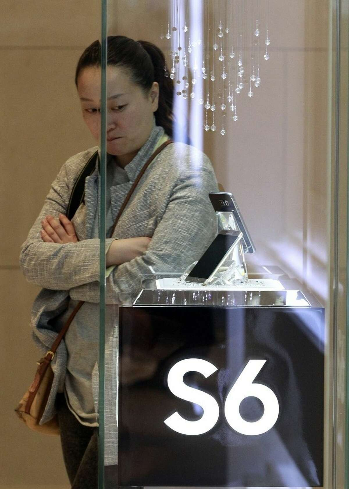 """A journalist looks at a Samsung Electronics Co.'s Galaxy S6 smartphone during its launch event at company's headquarter in Seoul, South Korea, Thursday, April 9, 2015. When Samsung dubbed development of its latest smartphones """"Project Zero,"""" it was sounding a note of desperation as sales tumbled and it lost pole position in the crucial Chinese market to rivals Xiaomi and Apple. (AP Photo/Ahn Young-joon)"""