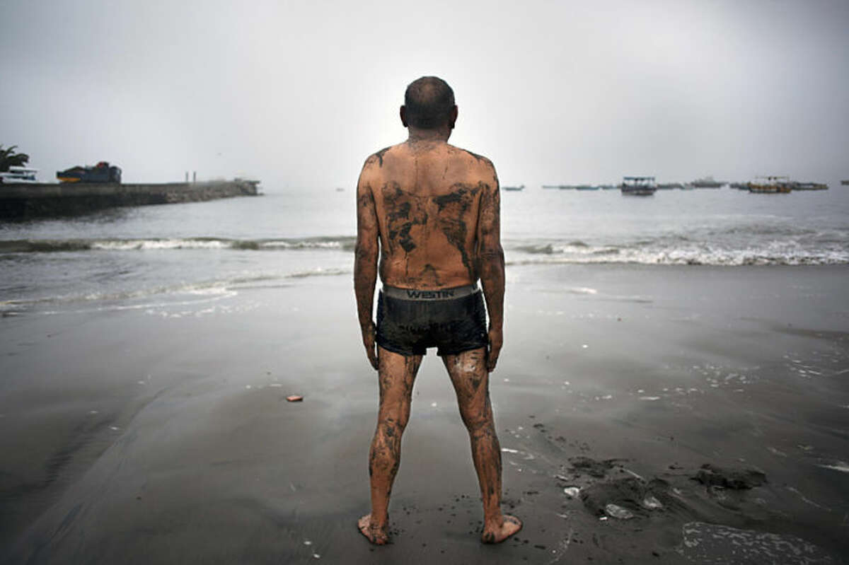 Teodocio Perez, 71, covered with a thin layer of wet sand, looks out at the Pacific Ocean during his morning exercises on the Playa de Pescadores shore in Lima, Peru, Wednesday, April 2, 2014. Chilean authorities discovered surprisingly light damage Wednesday from a magnitude-8.2 quake that struck in the Pacific Ocean, Tuesday evening, near the mining port of Iquique, about 87 miles from the Peruvian border. Tsunami warnings issued for Chile, Peru and Ecuador have been lifted. Six deaths have been reported. (AP Photo/Rodrigo Abd)