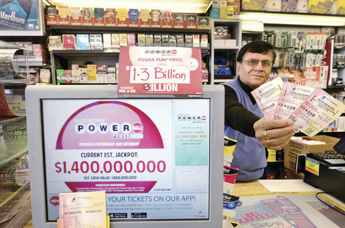 Hour photo/Erik Trautmann Upen Shah, owner of Crossroads Card and Gift, 280 Connecticut Ave., sells lottery tickets Tuesday for Wednesday's record-breaking Powerball Jackpot which hit $1.5 billion as of Tuesday.