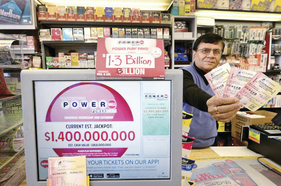 Hour photo/Erik TrautmannUpen Shah, owner of Crossroads Card and Gift, 280 Connecticut Ave., sells lottery tickets Tuesday for Wednesday's record-breaking Powerball Jackpot which hit $1.5 billion as of Tuesday.