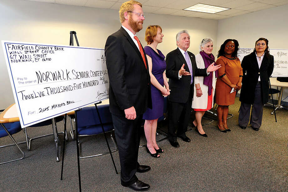 Hour photo / Erik Trautmann Mayor Harry W. Rilling presents Person-to-Person and the Norwalk Senior Center checks representing proceeds from the 2015 Mayor's Community Ball during a check presentation in Room 231 of City Hall Thursday monring. Norwalk Common Council member David McCarthy, Senior Center Director Beatrix Winter, Person-to-Person Execurtive Director CiCi Maher, Executive Assistant to the Mayor Sally Johnson and Administrative Assistant Maritza Albarado attended.