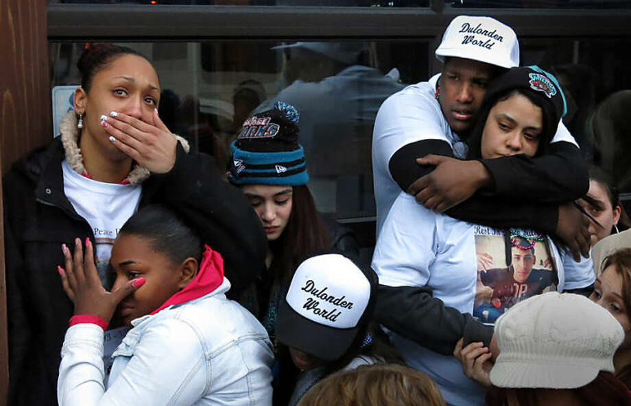 People grieve the loss of Dulonden Ratliff, 21, Kenosha, during a vigil held in his honor on Wednesday, April 2, 2014, on the site where he was fatally shot Saturday. (AP Photo/The Journal Times, Scott Anderson)