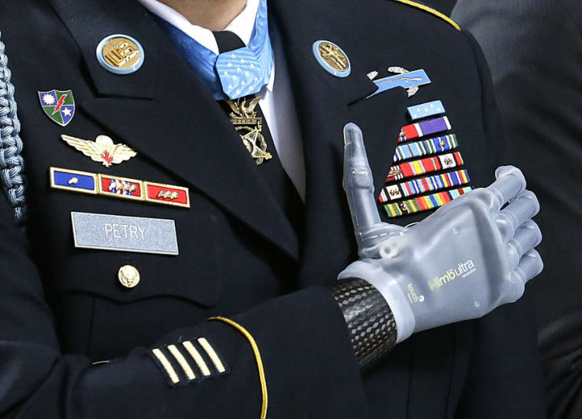 """Medal of Honor recipient Sgt. 1st Class Leroy Petry stands with his prosthetic hand over his heart and wears his Medal of Honor during the """"Pledge of Allegiance"""" Wednesday, April 2, 2014, at the Capitol in Olympia, Wash., during a ceremony to honor Petry and other recipients of the Medal of Honor who are from Washington state. Petry lost his hand in 2008 when an enemy grenade he was throwing away from fellow soldiers detonated while in combat in Afghanistan. (AP Photo/Ted S. Warren)"""