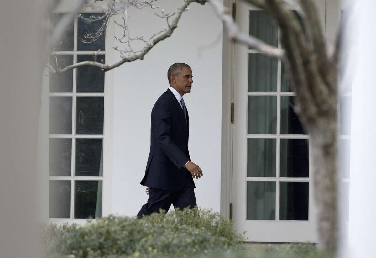 President Barack Obama walks along the colonnade of the White House in Washington, Tuesday, Jan. 12, 2016, to the residence from the Oval Office hours before giving his State Of The Union address. (AP Photo/Carolyn Kaster)