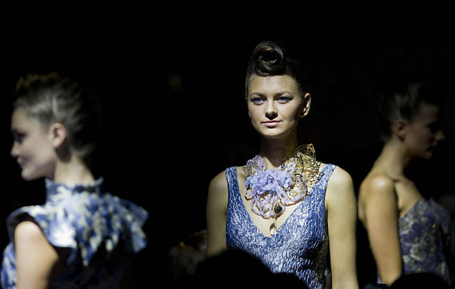 Three models wear a creation by Mexican designer Macario Jimenez at the Mecedes Benz Fashion Week in Mexico City, Wednesday, April 2, 2014. (AP Photo/Christian Palma)