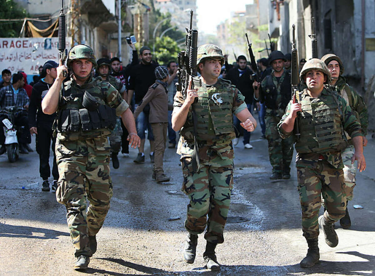 Lebanese army soldiers deploy in the streets of the Sunni neighborhood of Bab Tabbaneh and the neighboring Jabal Mohsen, which is mostly populated by followers of the Alawite sect, in the northern port city of Tripoli, Lebanon, Wednesday April, 2, 2014. In a rare day of exuberant emotion, weary residents of two warring neighborhoods greeted each other with tears and cheers as hundreds of Lebanese soldiers deployed for the first time in years throughout the area, quelling violence between them that has killed at least 200 people in three years. The Lebanese army deployment in the northern city of Tripoli is the most determined plan yet by the government to bring peace to an area that was teetering into the neighboring Syrian civil war. (AP Photo/Hussein Malla)
