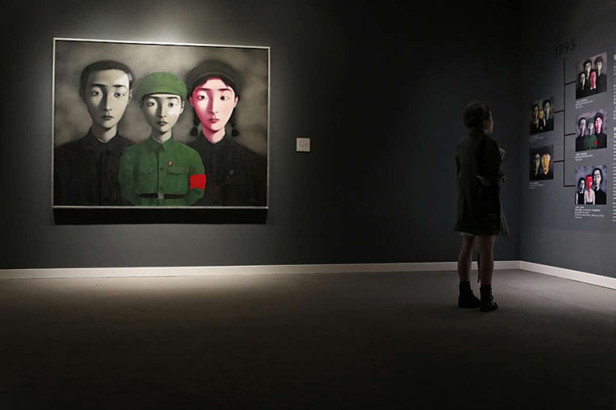 """A woman reads the introduction of the painting """"Bloodline: Big Family No.3"""" by Chinese artist Zhang Xiaogang during a preview for the Sotheby's Modern and Contemporary Asian Art Evening Sale in Hong Kong Wednesday, April 2, 2014. The painting is expected to fetch HK$65-80 million (US$8.3-10.3 million). (AP Photo/Kin Cheung)"""