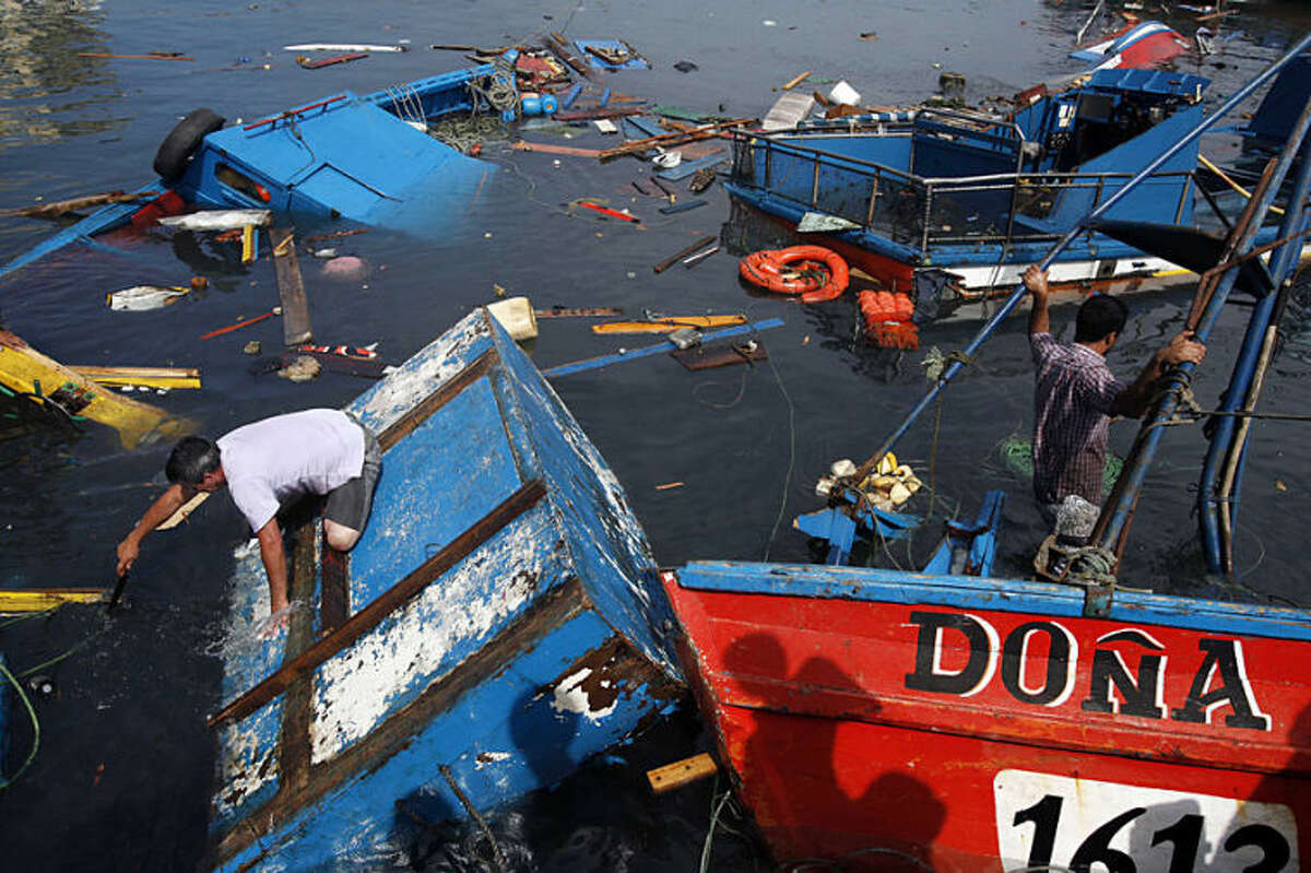 Fishermen look to salvage any remains destroyed overnight in the port of Iquique, Chile, Wednesday, April 2, 2014. Chilean authorities discovered surprisingly light damage Wednesday from a magnitude-8.2 quake that struck in the Pacific Ocean, Tuesday evening, near the mining port of Iquique, a northern coastal city of nearly 200,000 people. Fishing boats were lifted onto city streets and others were sunk in the port. Six deaths have been reported. ( AP Photo/ Luis Hidalgo, Pool)