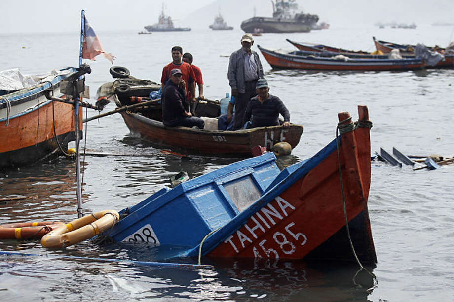 Fishermen look for boats to salvage damaged overnight in the port of Iquique, Chile, Wednesday, April 2, 2014. Chilean authorities discovered surprisingly light damage Wednesday from a magnitude-8.2 quake that struck in the Pacific Ocean, Tuesday evening, near the mining port of Iquique, a northern coastal city of nearly 200,000 people. Fishing boats were lifted onto city streets and others were sunk in the port. Six deaths have been reported. ( AP Photo/ Luis Hidalgo, Pool)