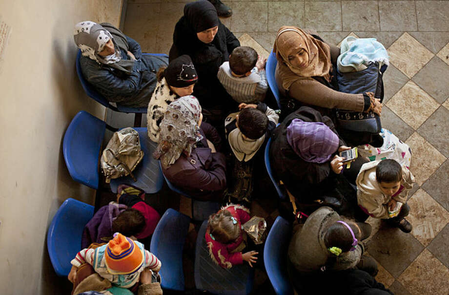 """FILE - In this Wednesday, Dec. 18, 2013, file photo, Syrian women wait with their children at the U.N. refugee agency's registration center in Zahleh, in Lebanon's Bekaa Valley. The number of Syrian refugees in Lebanon has surpassed 1 million, the U.N. refugee agency said Thursday, April 3, 2014, calling it a """"devastating milestone"""" for the tiny Arab country with about 4.5 million people of its own. (AP Photo/Maya Alleruzzo, File)"""