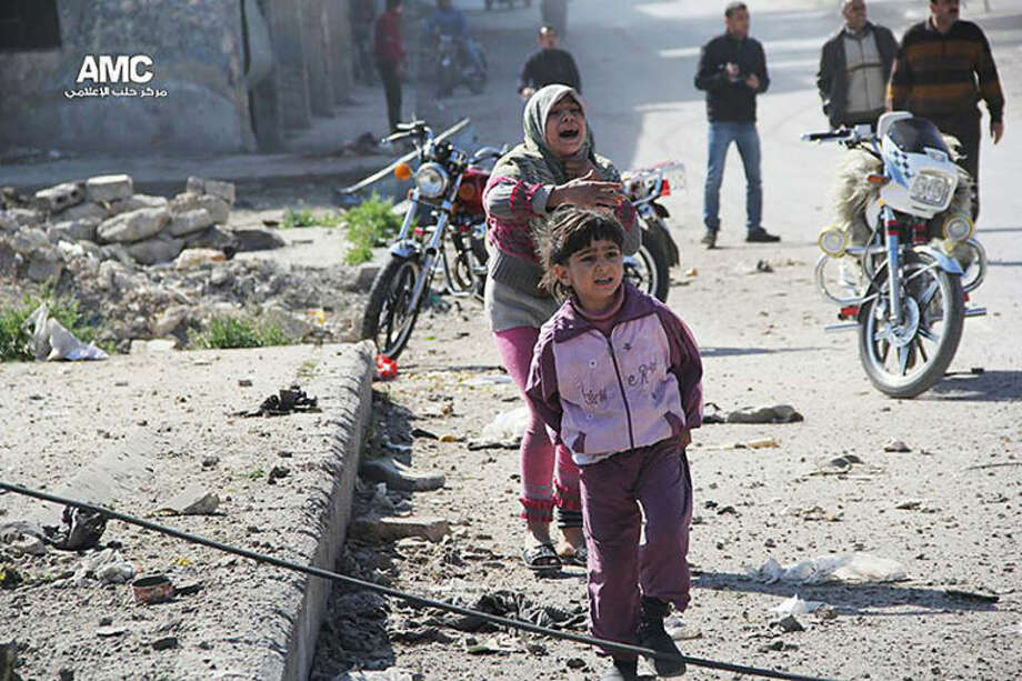 In this photo taken on Wednesday April 2, 2014 provided by the anti-government activist group Aleppo Media Center (AMC), an anti-Bashar Assad activist group, which has been authenticated based on its contents and other AP reporting, shows Syrian girls reacting after a government airstrike attack on their neighborhood, in Aleppo, Syria. (AP Photo/Aleppo Media Center, AMC)