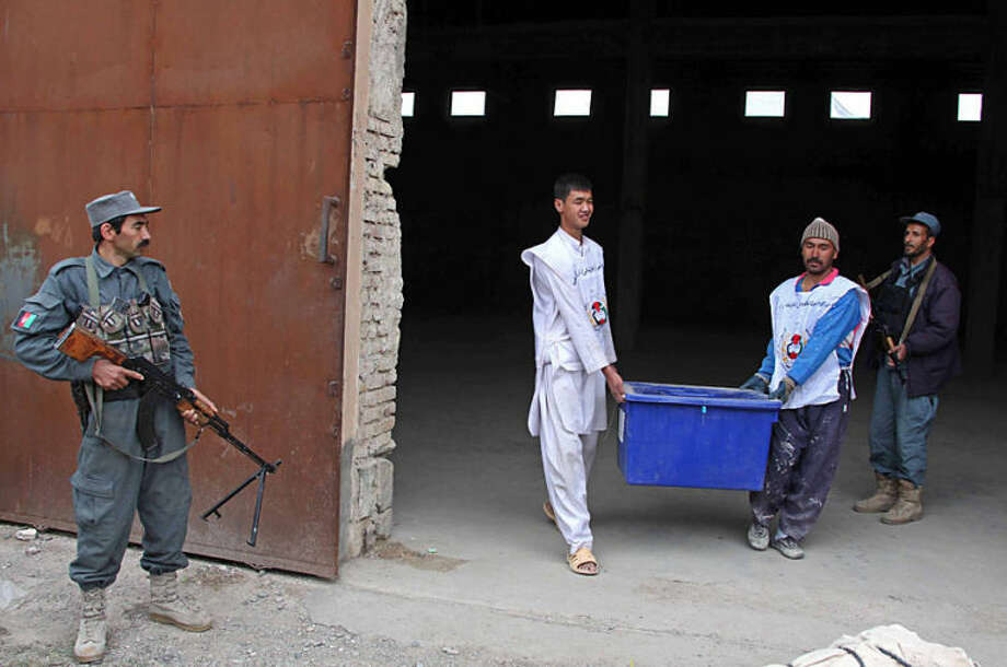 Afghan election workers prepare ballot boxes and election materials to be loaded into trucks and delivered to polling stations, at a warehouse in Herat, Afghanistan, Thursday, April 3, 2014. Elections will take place on Saturday. (AP Photo/Hoshang Hashimi)