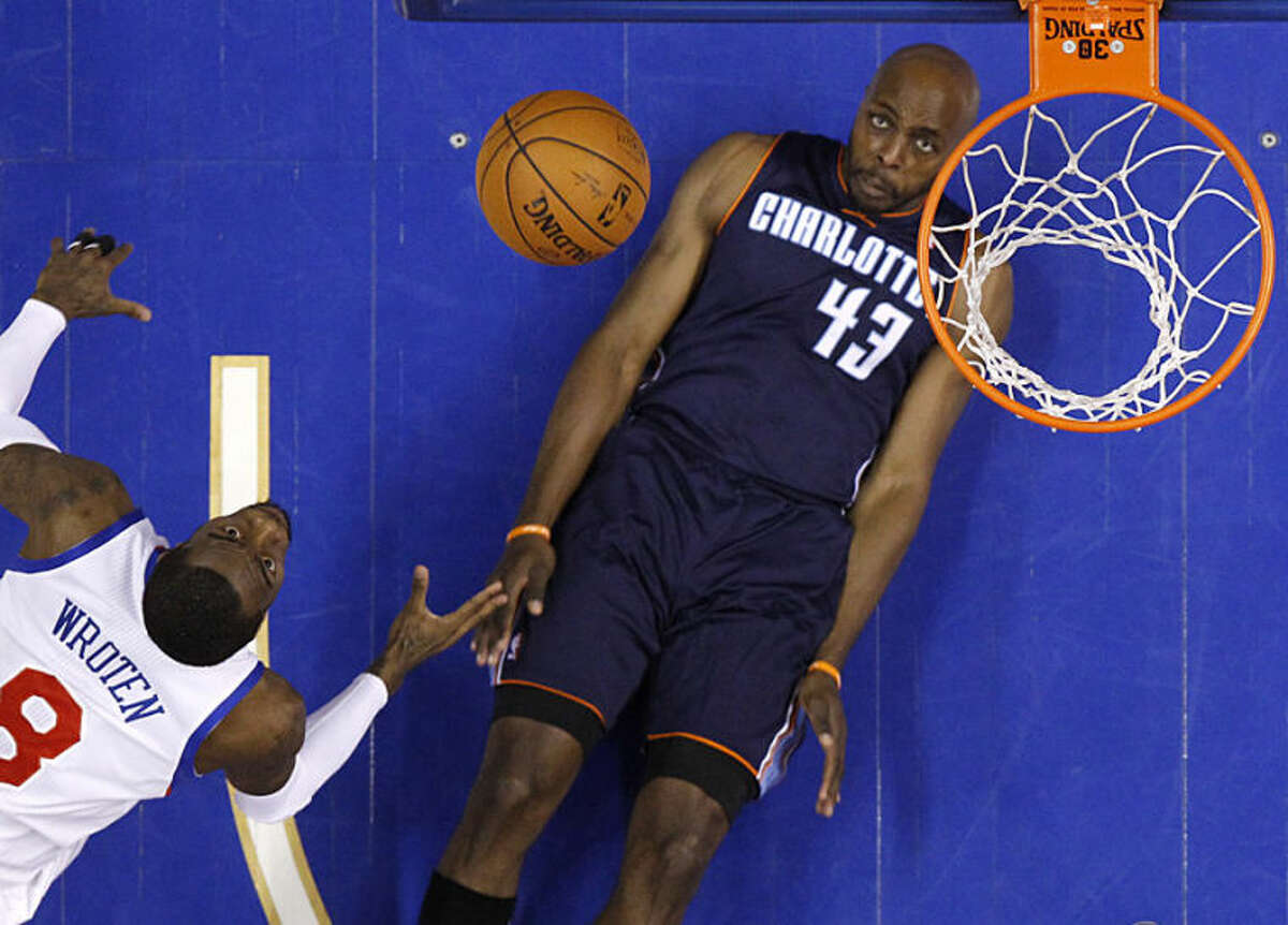 Philadelphia 76ers' Tony Wroten, left, and Charlotte Bobcats' Anthony Tolliver watch Wroten's shot go up during the second half of an NBA basketball game, Wednesday, April 2, 2014, in Philadelphia. Charlotte won 123-93. (AP Photo/Matt Slocum)