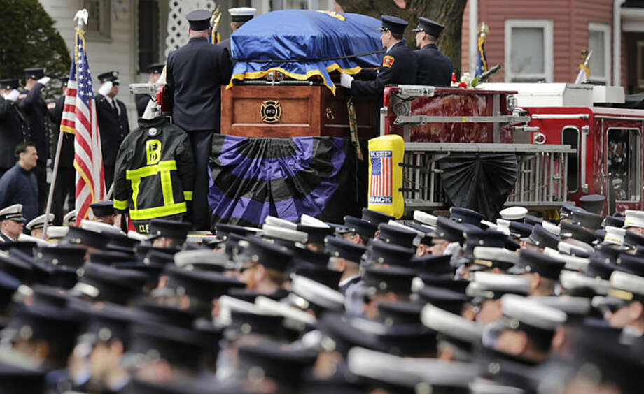 Firefighters salute as the casket of Boston Fire Lt. Edward Walsh is carried on Engine 33 as the funeral procession departs St. Patrick's Church in Watertown, Mass., Wednesday, April 2, 2014. Walsh and his colleague Michael Kennedy died after being trapped while battling a nine-alarm apartment fire in Boston on March 26. (AP Photo/Charles Krupa)
