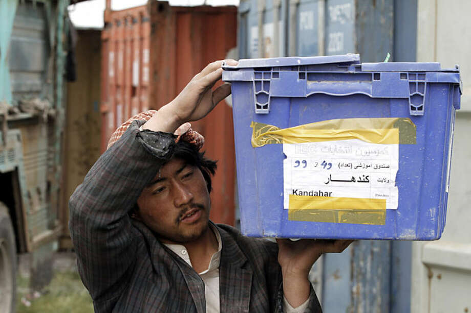An Afghan election worker carries election materials to be loaded into a trucks and delivered to polling stations, at a warehouse in Kandahar, Afghanistan, Thursday, April 3, 2014. Elections will take place on April 5. (AP Photo/Allauddin Khan)