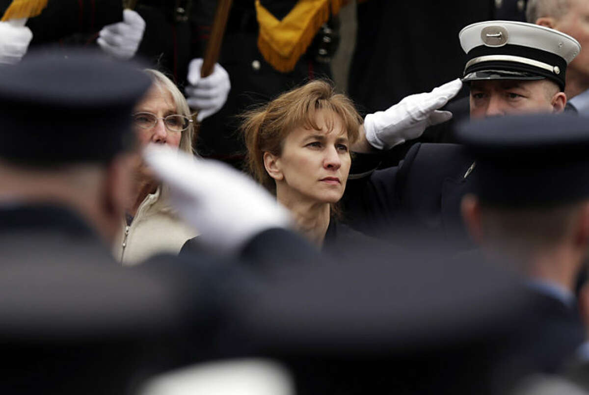 Firefighters salute as Kristen Walsh watches the casket of her late-husband Boston Fire Lt. Edward Walsh is lifted onto Engine 33 as the funeral procession prepares to depart St. Patrick's Church in Watertown, Mass., Wednesday, April 2, 2014. Walsh and his colleague Michael Kennedy died after being trapped while battling a nine-alarm apartment fire in Boston on March 26. (AP Photo/Charles Krupa)