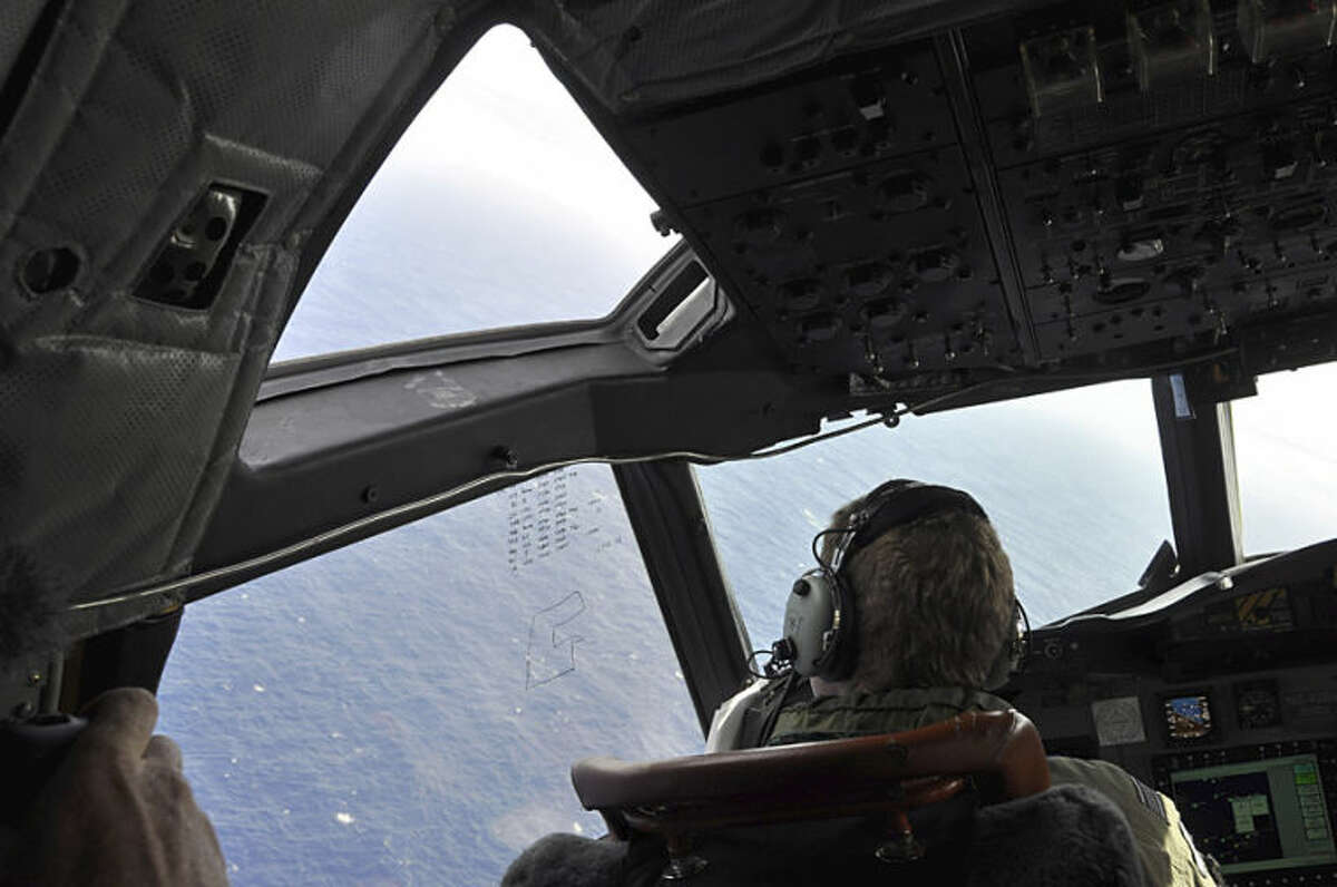 In this , Tuesday, April 1, 2014 photo made available Thursday, April 3, 2014, a crewman on a Royal New Zealand Air Force P-3 Orion Rescue Flight 795 searches for debris from the missing Malaysia Airlines Flight MH370, in southern Indian Ocean, 1,500 kilometers northwest of Perth, Australia. The focus of the search has changed repeatedly in the nearly four weeks since the air traffic controllers lost contact with the Boeing 777 between Malaysia and Vietnam over the South China Sea. It began in the South China Sea, then shifted toward the Malacca Strait to the west, where Malaysian officials eventually confirmed that military radar had detected the plane. (AP Photo/AAP Image, Kim Christian, POOL)