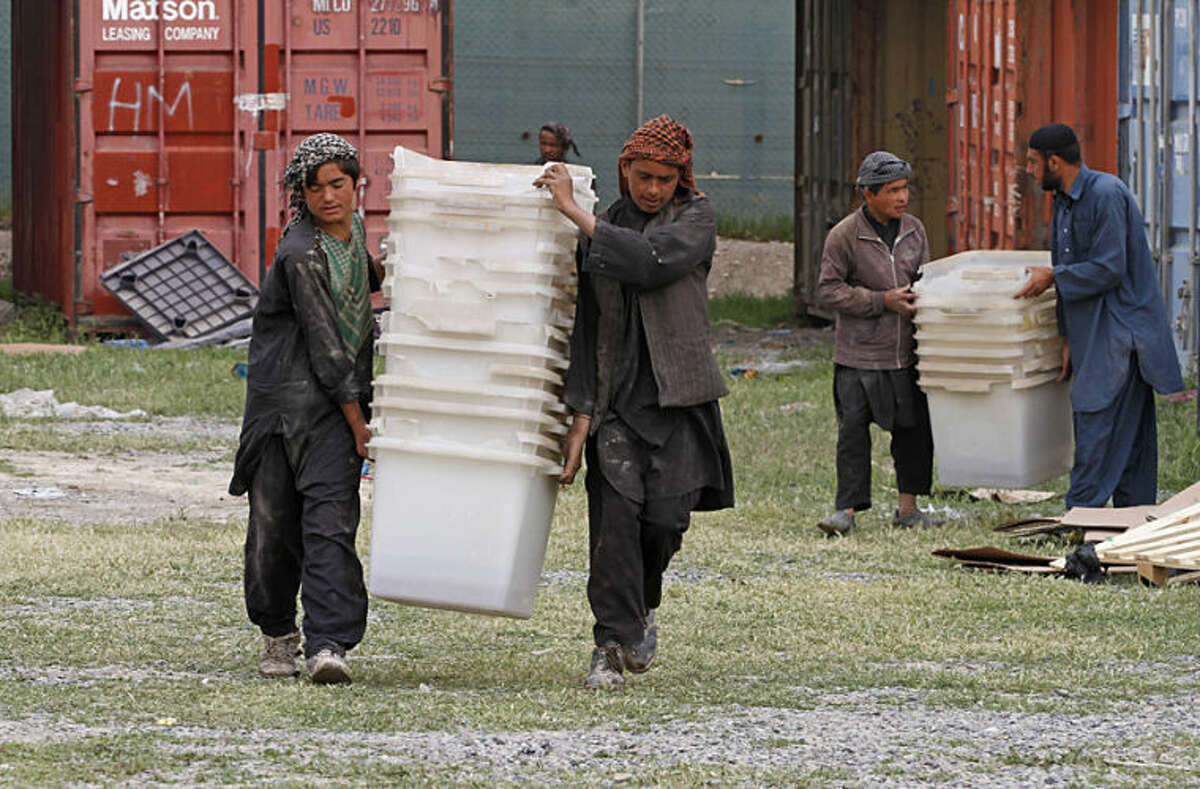 Afghan election workers prepare ballot boxes and election materials to be loaded into trucks and delivered to polling stations, at a warehouse in Kandahar, Afghanistan, Thursday, April 3, 2014. Elections will take place on April 5. (AP Photo/Allauddin Khan)