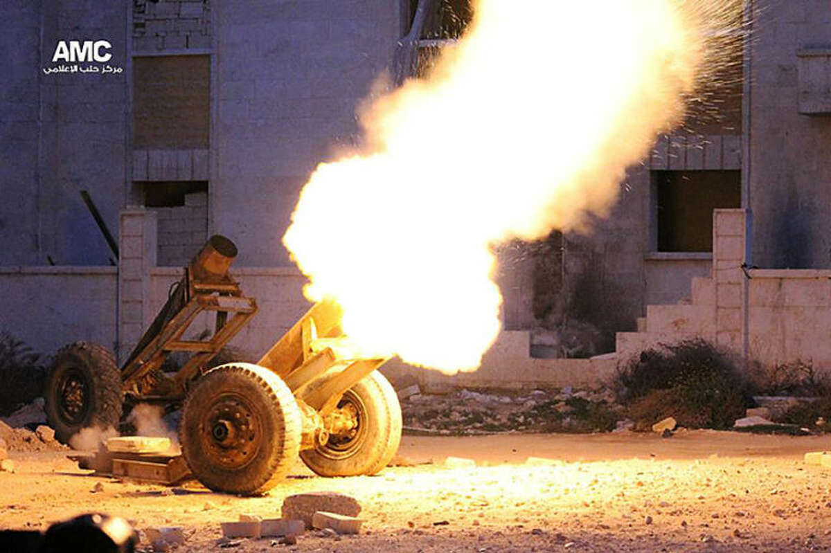 """This Wednesday April 2, 2014, photo provided by the anti-government activist group Aleppo Media Center (AMC), an anti-Bashar Assad activist group, which has been authenticated based on its contents and other AP reporting, shows locally made shells which rebels call a """"Hell Cannon,"""" is fired by rebels against the Syrian government forces, in Aleppo, Syria. (AP Photo/Aleppo Media Center, AMC)"""