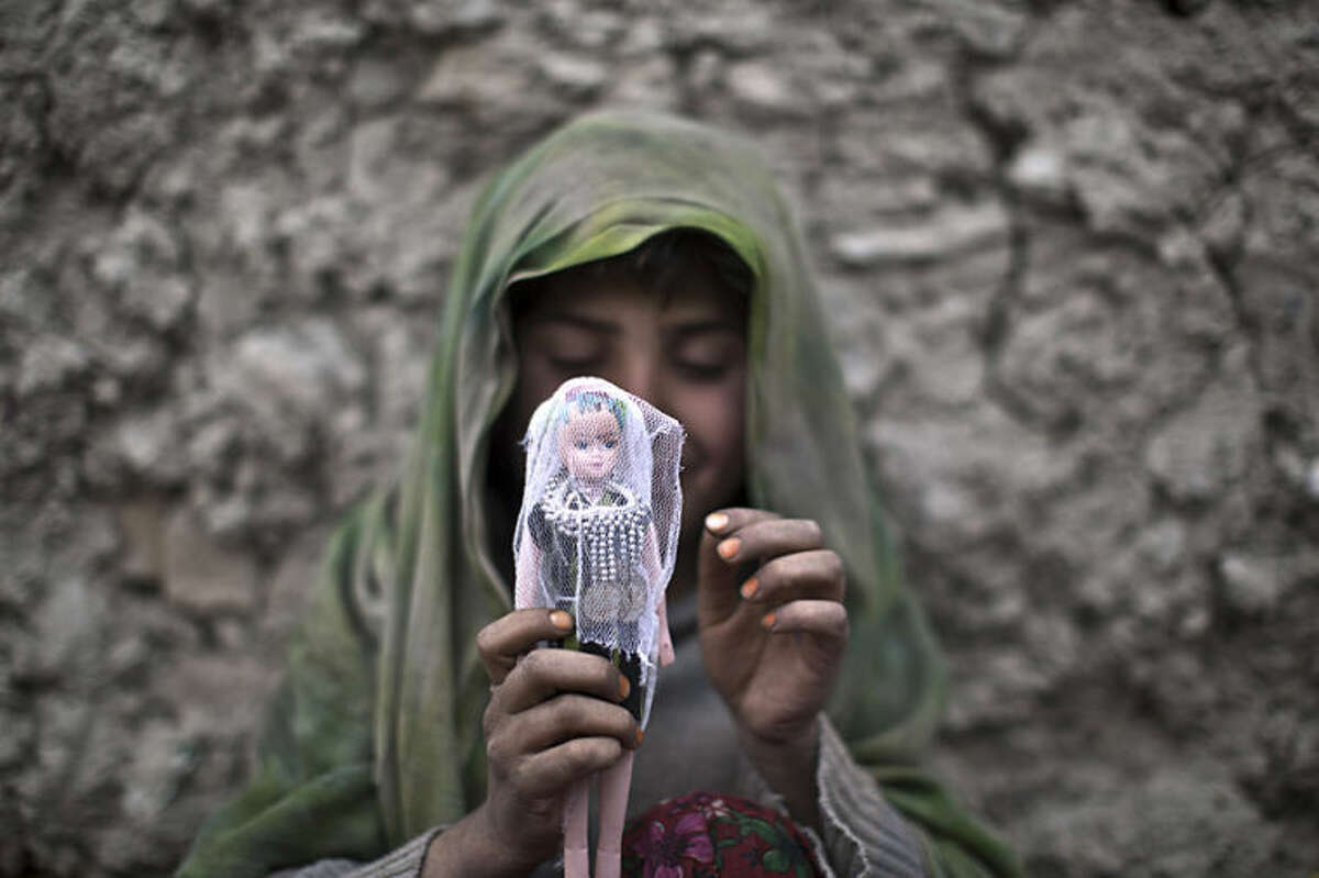An Afghan girl sits on the ground dressing her doll while playing in an alley in Kabul, Afghanistan, Thursday, April 3, 2014. (AP Photo/Muhammed Muheisen)