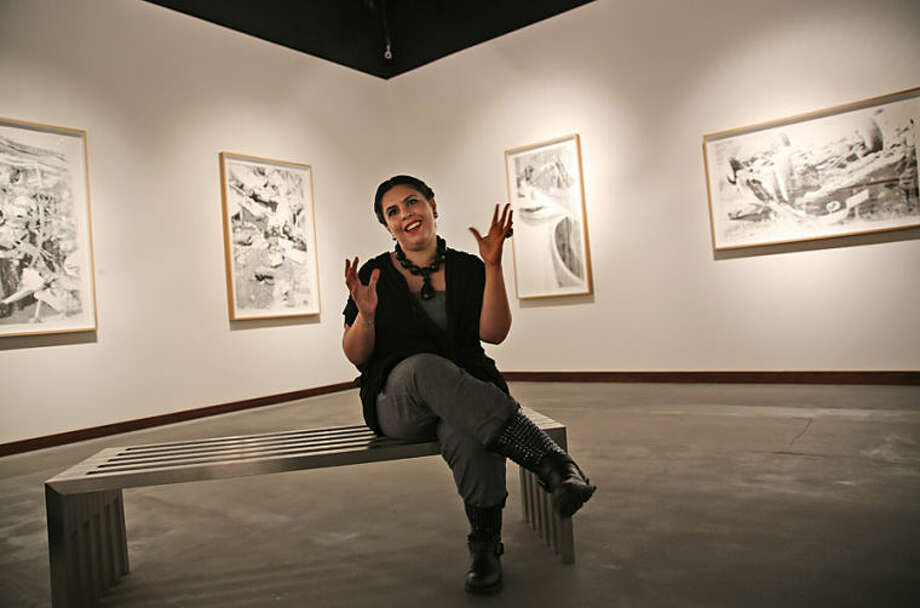 """In this Wednesday, March 26, 2014, Saudi artist Manal Al-Dowayan talks to the Associated Press at her exhibition titled """"Crash"""" in the Cuadro gallery in Dubai, United Arab Emirates. Al-Dowayan's exhibitions focus on women's rights in Saudi Arabia. Her current exhibition is a research-based collection that exposes the ways in which Saudi women are rendered voiceless and nameless in news clippings about their death. (AP Photo/Kamran Jebreili)"""