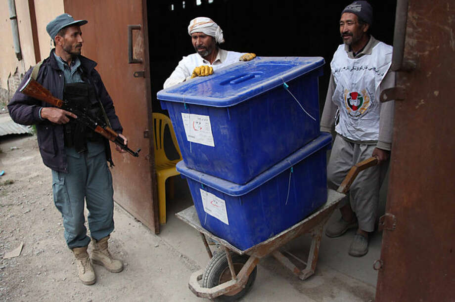 Afghan election workers prepare ballot boxes and election materials to be loaded into trucks and delivered to polling stations, at a warehouse in Herat, Afghanistan, Thursday, April 3, 2014. Elections will take place on April 5. (AP Photo/Hoshang Hashimi)