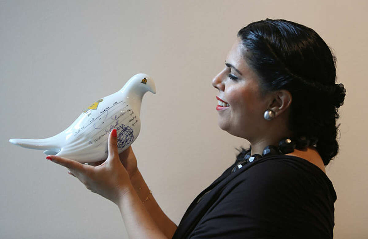 """In this Wednesday, March 26, 2014 photo, Saudi artist Manal Al-Dowayan poses with one of her messenger pigeons of """"Suspended Together"""" installation at her exhibition titled """"Crash"""" at the Cuadro Art Gallery in Dubai, United Arab Emirates. The kingdom's modern art scene has become a platform for Saudi artists to voice their frustration about the country's most sensitive issues without coming into friction with the country's rulers, reaching the public in new says and allowing individual points of view in a country where dominant ultraconservative norms have long prevailed. (AP Photo/Kamran Jebreili)"""