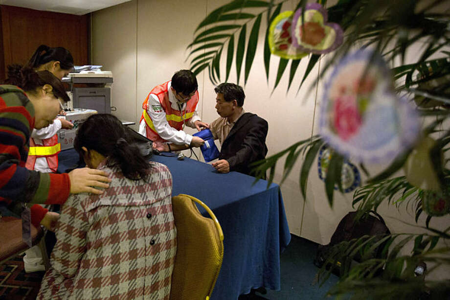 Relatives of the Chinese passengers onboard the Malaysia Airlines flight MH370 seek medical attention in a prayer room in Beijing Thursday, April 3, 2014. No trace of the Boeing 777 has been found nearly a month after it vanished in the early hours of March 8 on a flight from Kuala Lumpur to Beijing with 239 people on board. (AP Photo/Ng Han Guan)