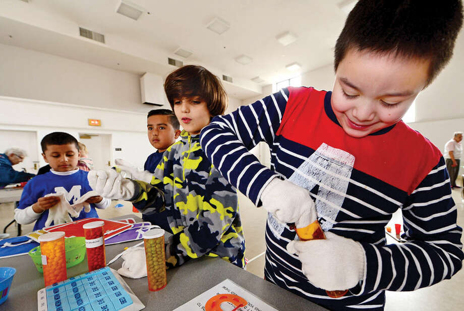 """Hour photo / Erik Trautmann Marvin Elementary School students including, Jonathan Ordonez and David Sevilla, try to open pill bottles with a disability as they participate in the """"The Big Event"""" at The Marvin senior facility Thursday. The culmination event explores and challenges the stereotyping of the elderly while promoting bonding between the generations following a year where the 2nd and 4th grade students met monthly with seniors at The Marvin with a goal of helping youngsters understanding aging."""