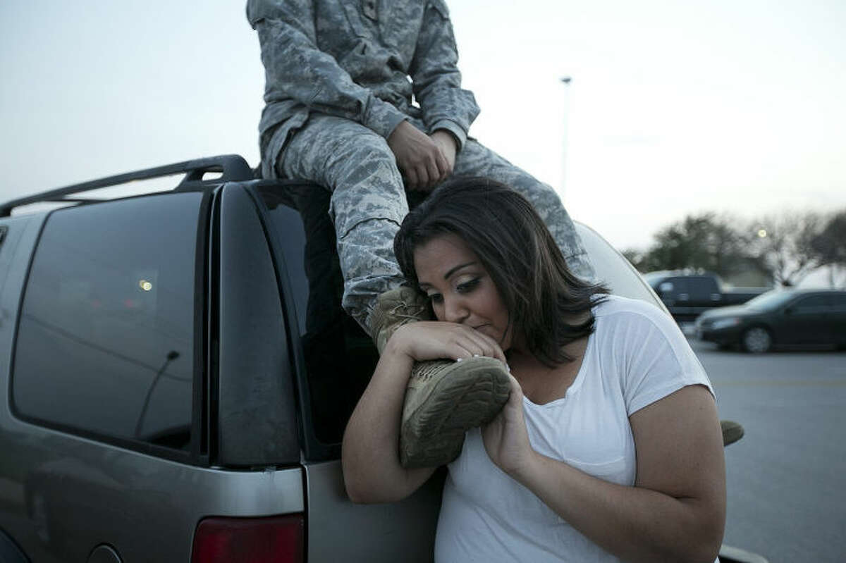 Lucy Hamlin leans on her husband's foot, Specialist Timothy Hamlin, as they wait to be allowed back onto Fort Hood, Texas, where they reside on Wednesday, April 2, 2014. A shooting occurred on the base with at least four dead and 14 injured according to the officials. (AP Photo/Austin American-Statesman, Deborah Cannon)
