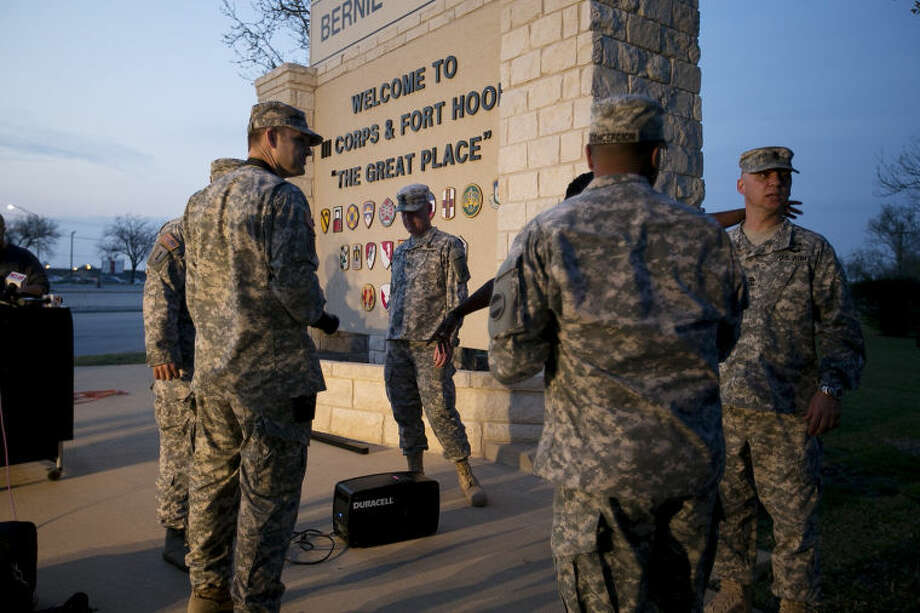 Military personnel wait for a news conference to begin at Fort Hood, Texas, on Wednesday, April 2, 2014. A gunman opened fire in an attack that left four people killed including the shooter, at the same post where more than a dozen people were killed in a 2009 mass shooting, law enforcement officials said. The gunman died of a self-inflicted gunshot wound, officials said. At least 14 people were hurt in the shooting. (AP Photo/Austin American-Statesman, Deborah Cannon)