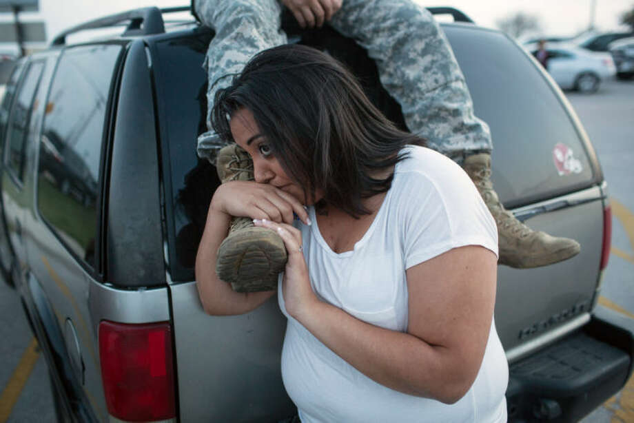 Lucy Hamlin and her husband, Spc. Timothy Hamlin, wait for permission to re-enter the Fort Hood military base, where they live, following a shooting on the base, Wednesday, April 2, 2014, in Fort Hood, Texas. (AP Photo/ Tamir Kalifa)