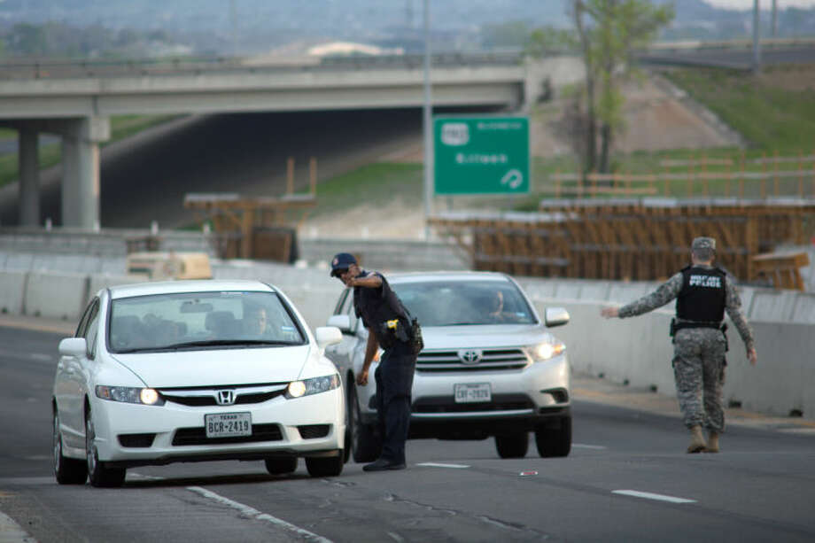 Local and Military police direct traffic outside of an entrance to Fort Hood following reports of an active shooting on the military base in Wednesday, April 2, 2014, in Fort Hood, Texas. (AP Photo/Tamir Kalifa)
