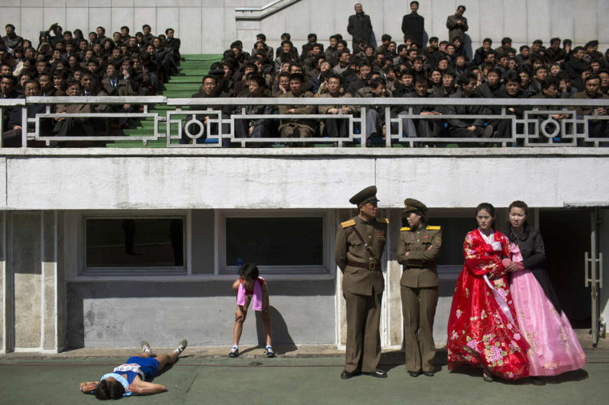 FILE - In this April 14, 2013 file photo, runners rest inside Kim Il Sung Stadium in Pyongyang as North Korea hosts the 26th Mangyongdae Prize Marathon to mark the birthday of the late leader Kim Il Sung on April 15. For the first time ever, North Korea is opening up the streets of its capital to runner-tourists for the annual Pyongyang marathon, undoubtedly one of the most exotic feathers in any runner?'s cap. Tourism companies say they have been inundated by requests to sign up for the April 13, 2014 event, which this year will include amateur runners from around the world. (AP Photo/David Guttenfelder, File)
