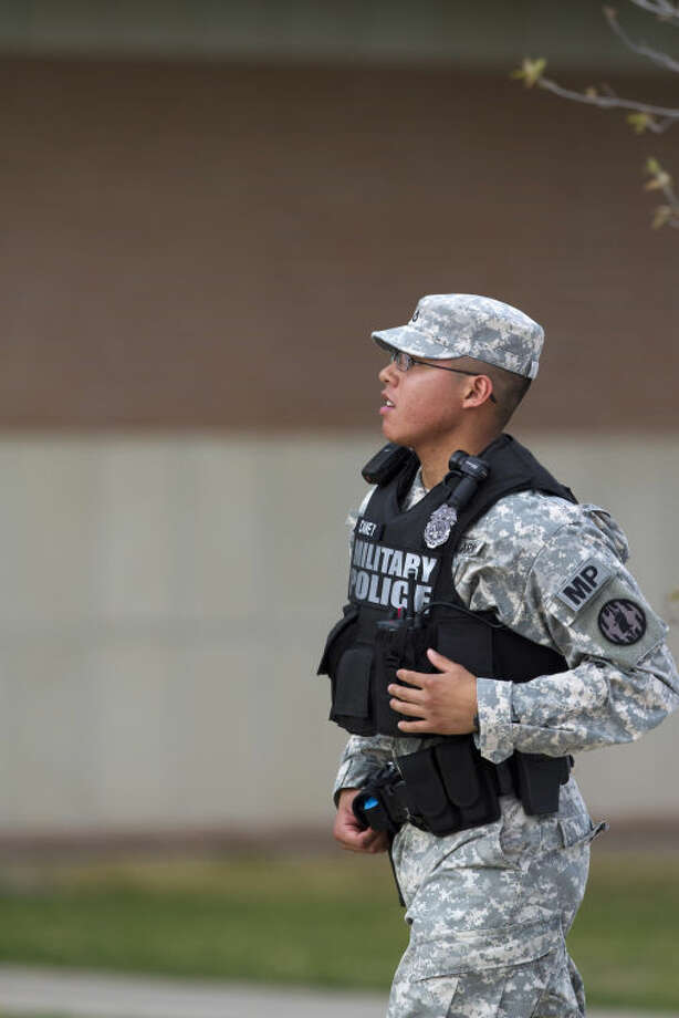 A Military Police officer runs toward the road leading to the Main Gate, Wednesday, April 2, 2014, as an active shooter remains at large at Fort Hood, Texas. One person was killed and 14 injured in the shooting, and officials at the base said the shooter is believed to be dead. The details about the number of people hurt came from two U.S. officials who spoke on condition of anonymity because they were not authorized to discuss the information by name. (AP Photo/The Temple Daily Telegram, Rusty Schramm)