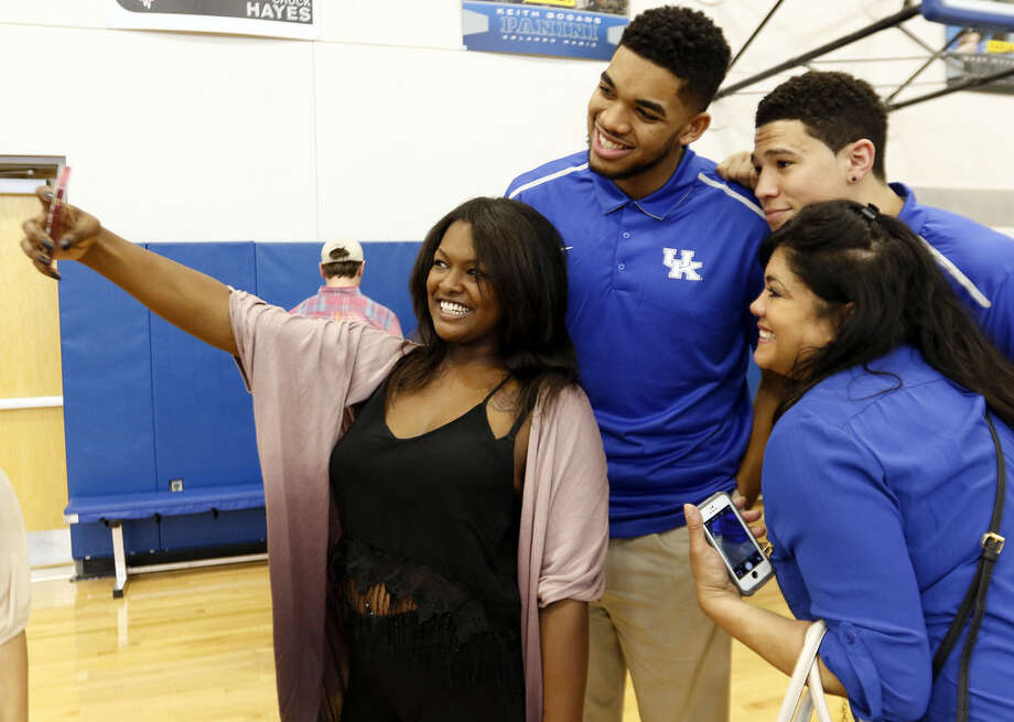 Kentucky NCAA college basketball players, top left, Karl-Anthony Towns, top right, Devin Booker take a selfie with Karl-Anthony's girlfriend, left, India Gentry and his mother Jacqueline Cruz-Towns after the players announced their intent to place their names in the NBA draft during a news conference at the Joe Craft Center, Thursday, April 9, 2015, in Lexington, Ky. (AP Photo/James Crisp)