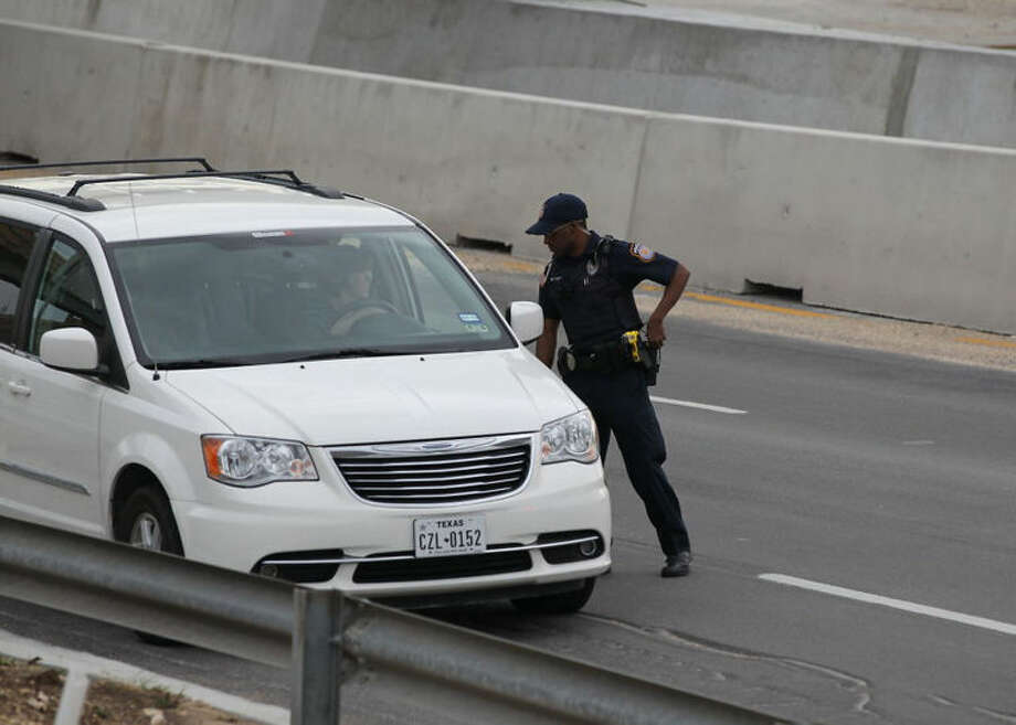 A police officer checks drivers' IDs outside the main gate at Fort Hood, Texas, after a shooting at the Army base Wednesday, April 2, 2014. At least one person was killed and at least 14 injured in a shooting Wednesday at Fort Hood. (AP Photo/Austin American-Statesman, Deborah Cannon) AUSTIN CHRONICLE OUT, COMMUNITY IMPACT OUT, MAGS OUT; NO SALES; INTERNET AND TV MUST CREDIT PHOTOGRAPHER AND STATESMAN.COM