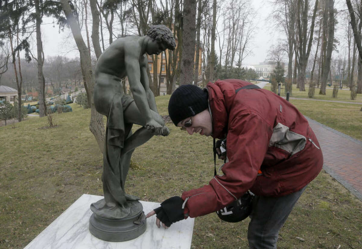 """FILE - In this Saturday, Feb, 22, 2014 file photo a visitor looks at a sculpture in the grounds of of the then Ukrainian President Yanukovych's countryside residence in Mezhyhirya, which is about 20 km (12.5 miles) north of the capital Kiev. Ukraine's ousted president, Viktor Yanukovych, said Wednesday April 2, 2014, that he was """"wrong"""" to invite Russian troops into Crimea, and vowed to try to persuade Russia to return the Black Sea peninsula. In his first interview since fleeing to Russia in February, Yanukovych told The Associated Press and Russia's state NTV television that he still hopes to negotiate with Russian President Vladimir Putin to get back the coveted region. Asked about his opulent country residence outside of Kiev a complex that shocked crowds of Ukrainians with its extravagant display of wealth amid the country's financial ruin Yanukovych denied any allegations of corruption. He spoke with pride about his collection of dozens of old-time cars, but said he hadn't seen or used the golden loaf of bread found in his residence that has attracted much attention and sarcasm. (AP Photo/Efrem Lukatsky, File)"""