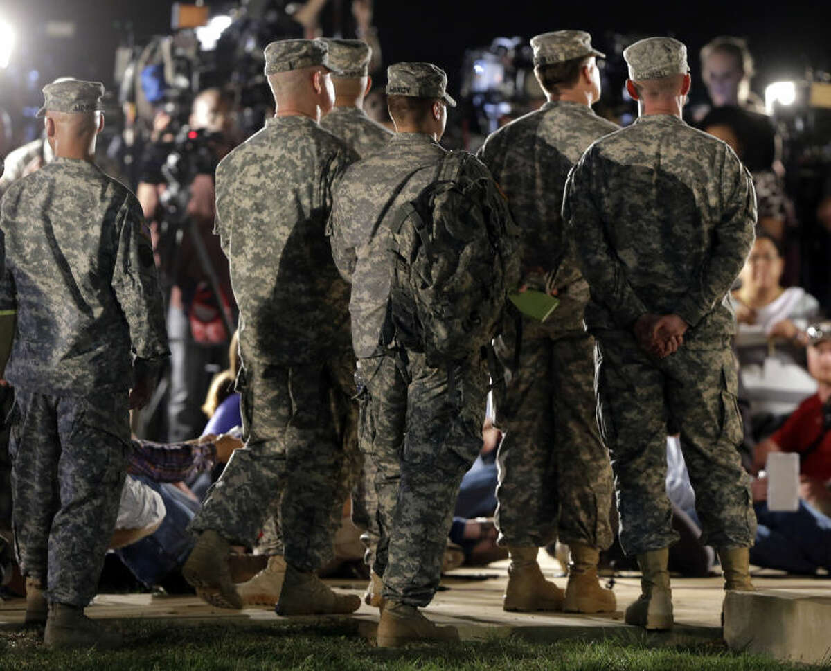 Soldiers listen in the wings as Lt. Gen. Mark Milley address the media during a news conference at the main gate to Fort Hood, Wednesday, April 2, 2014, in Fort Hood, Texas. A soldier opened fire Wednesday on fellow service members at the military base, killing three people and wounding 16 before committing suicide, authorities said. (AP Photo/Eric Gay)