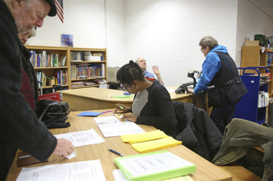 Khadijat Bgenro signs in voters for the District A Democrats competing for 11 seats on the Norwalk Democratic Town Committee during caucus Wednesday at Kendall School.Hour Photo / Danielle Calloway