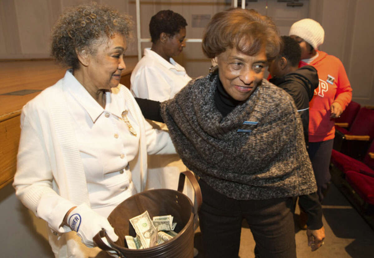 Hour photo/Chris Palermo. Betty Maharaja greets Jean Carter, Fairfield County Calvary Baptist Church usher at the city-wide memorial observance of the national holiday honoring Rev. Dr. Martin Luther King, Jr. Monday night at Norwalk City Hall.