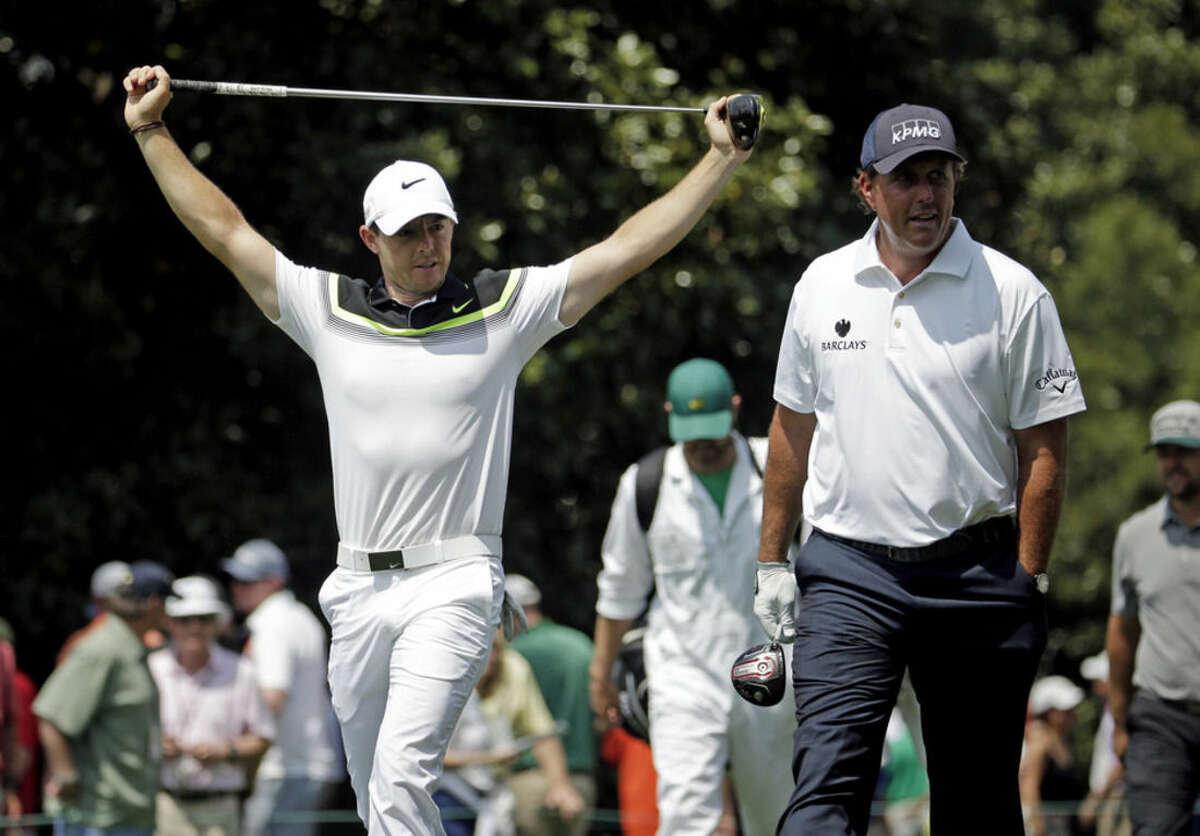 Rory McIlroy, of Northern Ireland, and Phil Mickelson walk down the ninth fairway during the first round of the Masters golf tournament Thursday, April 9, 2015, in Augusta, Ga. (AP Photo/Charlie Riedel)