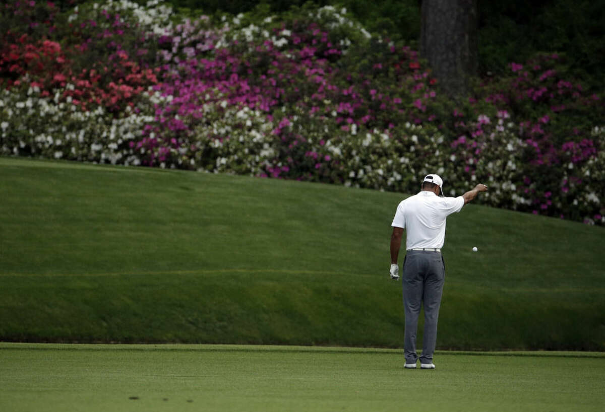 Tiger Woods takes a drop after hitting into a creek on the 12th hole during the first round of the Masters golf tournament Thursday, April 9, 2015, in Augusta, Ga. (AP Photo/Charlie Riedel)