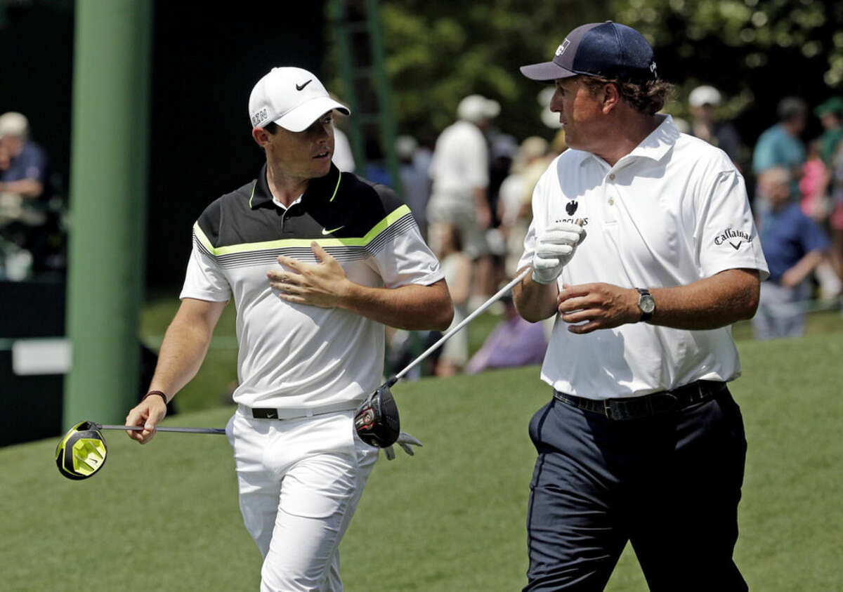 Rory McIlroy, of Northern Ireland, walks down the ninth fairway with Phil Mickelson, right, during the first round of the Masters golf tournament Thursday, April 9, 2015, in Augusta, Ga. (AP Photo/Charlie Riedel)