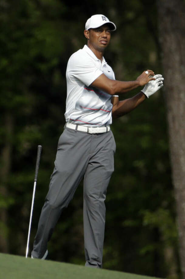 Tiger Woods drops his club after hitting on the 11th fairway during the first round of the Masters golf tournament Thursday, April 9, 2015, in Augusta, Ga. (AP Photo/Charlie Riedel)